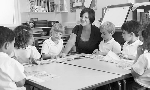 Students and Teacher around a table in classroom